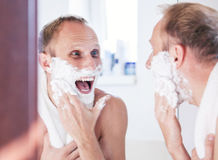 Happy man shaving in bathroom Royalty Free Stock Photo