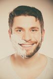 Happy man with shaving cream foam on half of face. Stock Photography