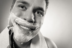 Happy man shaving using razor with cream foam. Handsome guy removing face beard hair. Skin care and hygiene royalty free stock photos