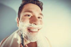 Happy man shaving using razor with cream foam. Stock Photography