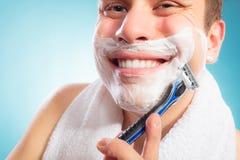 Happy man shaving using razor with cream foam. Royalty Free Stock Photos