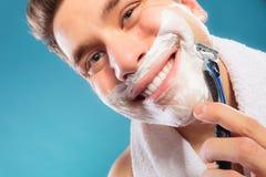 Happy man shaving using razor with cream foam. Stock Photos