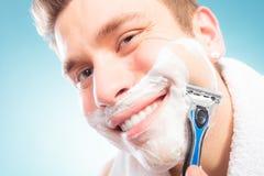 Happy man shaving using razor with cream foam. Royalty Free Stock Image