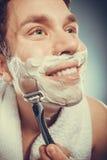 Happy man shaving using razor with cream foam. Royalty Free Stock Images