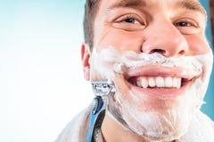 Happy man shaving using razor with cream foam. Royalty Free Stock Photography