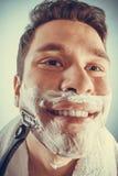 Happy man shaving using razor with cream foam. Stock Image