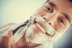 Happy man shaving using razor with cream foam. Stock Photo