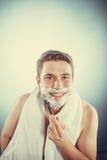 Happy man shaving using razor with cream foam. Stock Images