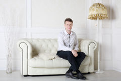 Happy man in shirt and pants sits on white leather sofa Royalty Free Stock Image