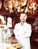 Happy man shop assistant using scales for meat in butcher's sh Royalty Free Stock Photos