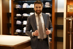 Happy man in shop. Happy bearded man in suit posing in shop while holding his jacket and looking at camera Royalty Free Stock Photography