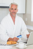 Happy man shopping online at breakfast in a bathrobe Royalty Free Stock Image