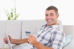 Happy man shopping online through laptop using credit card Stock Photos