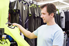 Happy man shopping for sport t-shirt in shop Stock Photos