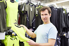 Happy man shopping for sport t-shirt in shop. Happy man shopping for t-shirt in sport shop Royalty Free Stock Image