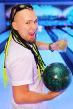 Happy man shouts, holds ball and glass in bowling. Happy young man shouts, holds ball and glass of cocktail in bowling club Royalty Free Stock Image