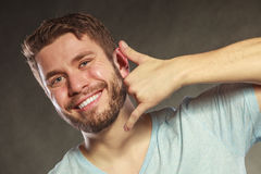 Happy man showing call me gesture. Royalty Free Stock Photography