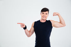 Happy man showing his biceps and pointing finger at copyspace Royalty Free Stock Photos
