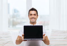 Happy man showing laptop blank screen at home Royalty Free Stock Photography
