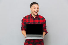 Happy man showing laptop computer screen at camera Stock Photo