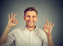 Happy man showing OK gesture with hands. Portrait of happy man showing OK gesture with hands  on gray background Stock Photos