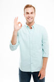 Happy man showing ok sign with fingers over white background Stock Photography