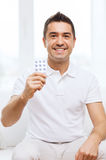Happy man showing pack of pills at home Royalty Free Stock Photos