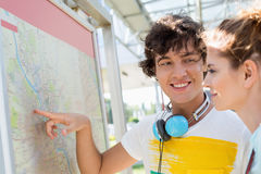 Happy man showing places on map to woman outdoors Royalty Free Stock Images