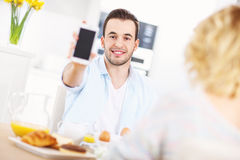 Happy man showing smart phone Royalty Free Stock Photos