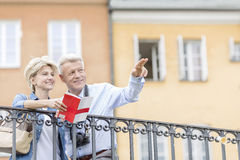 Happy man showing something to woman with guidebook in city Stock Image