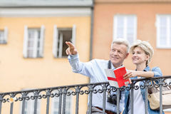 Happy man showing something to woman with guidebook in city. Happy men showing something to women with guidebook in city royalty free stock images