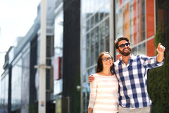 Happy man showing something to woman outside building Royalty Free Stock Photos