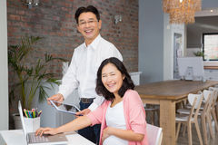 Happy man showing tablet to his pregnant wife Stock Image