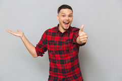 Happy man showing thumb up and holding copyspace on pound Stock Photography