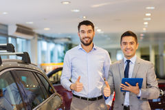 Happy man showing thumbs up in auto show or salon Royalty Free Stock Image
