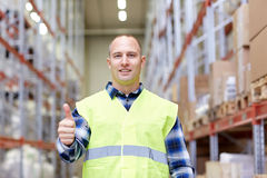 Happy man showing thumbs up gesture at warehouse Stock Images