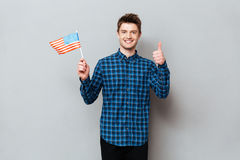 Happy man showing thumbs up and holding USA flag. Photo of young happy man standing over grey wall and looking at camera while showing thumbs up and holding USA royalty free stock image