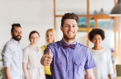 Happy man showing thumbs up over team in office Stock Photo