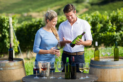 Happy man showing wine bottle to woman while standing by table Stock Image