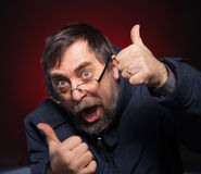 Happy man shows ok sigh on a red Royalty Free Stock Images