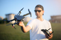 Happy man shows small compact drone and holds remote controller in his hand. Pilot looks at quadcopter before the launch Stock Photo