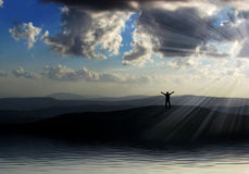Happy man silhouette on the mountains against bea. Utiful sky with sun rays Stock Photo