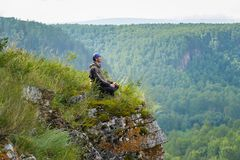 Happy man sits on the edge of a cliff above the forest, leisure in harmony with nature Stock Photos