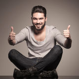 Happy man sits and make the ok hand sign Royalty Free Stock Images