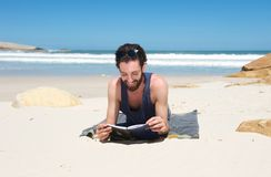 Happy man sitting on the beach reading a book Stock Photos