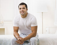 Happy Man Sitting on Bed Stock Photography