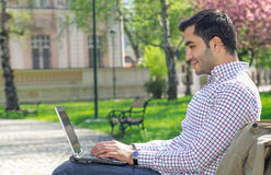 Happy man sitting on bench and using laptop Stock Photo