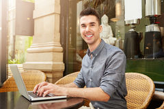 Happy man sitting at cafe working on laptop outside. Portrait of happy man sitting at cafe working on laptop outside Stock Image