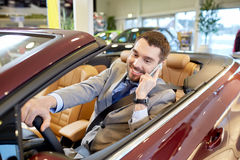 Happy man sitting in car at auto show or salon Stock Photo