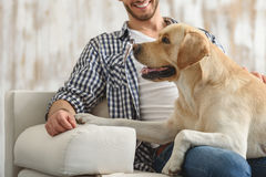 Happy man sitting on a couch with his pet friend. Side view of a puppy lying on owner's knees at home Royalty Free Stock Photo
